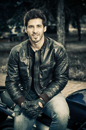 Sexy biker man wearing jeans and leather jacket sitting relaxed on his motorcycle. Banco de Imagens - 61535655