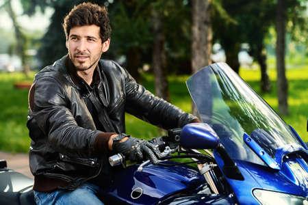 hombre motorista hermoso que desgasta la chaqueta de cuero negro en una motocicleta. Foto de archivo