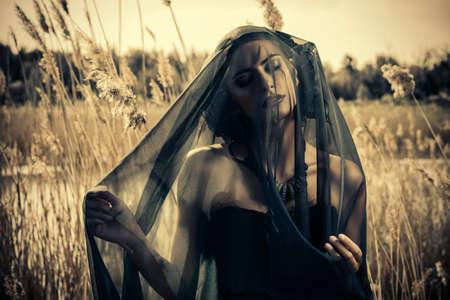 Mooie donkerbruine vrouw die lange zwarte jurk en zwarte sluier stellen tussen het riet. De oude tijden, de gotische stijl. Mode.