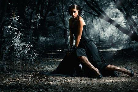 美しいゴシック女性の神秘的な森でポーズをとって長い黒のドレスを着ています。中世の歴史。ファッション。