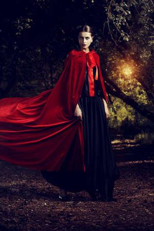 아름 다운 갈색 머리 여자 검은 구식 드레스와 마법의 숲의 덤 불에서 산책하는 빨간색 망 토에. 고딕 스타일. 유행.