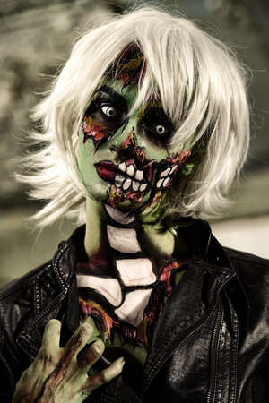 Terrible bloodthirsty zombie woman in the slums. Body-painting project. Glamorous zombie girl. Halloween make-up. Horror. Stock Photo