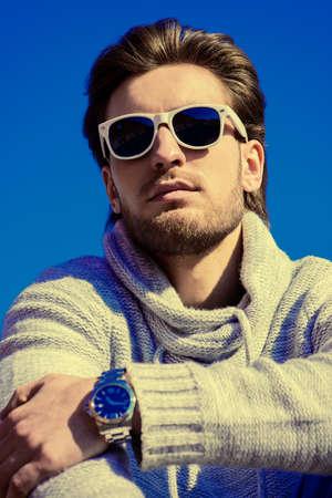 Junger stattlicher Mann in Freizeitkleidung und Sonnenbrillen über blauen Himmel. Herren Schönheit, Mode. Outdoor-Porträt. Standard-Bild