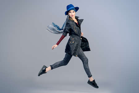 Studio fashion shot. Beautiful female model posing at studio in motion.