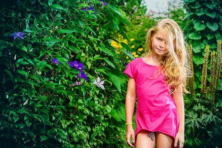 La ragazza sveglia ridendo si diverte in un parco d'estate. Infanzia felice. Vacanze estive.