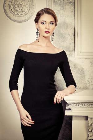 Affascinante giovane donna che indossa abito nero raccordo. Gioielleria. Moda girato.