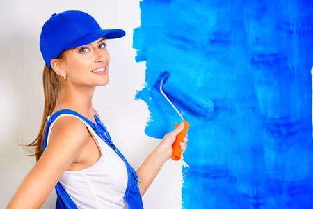 新しいアパートで壁の絵画幸せな笑みを浮かべて女。女性画家のオーバー オールでは、青の色で壁を描画します。職業。 写真素材