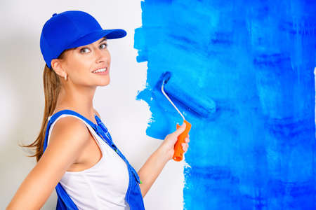 Happy smiling woman painting walls in new apartments. Woman painter in overalls paints the wall in blue color. Occupation.