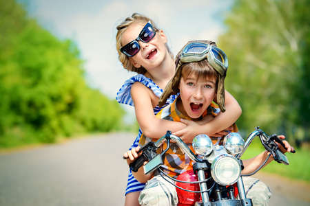 Happy kids go on a journey on a motorcycle on a bright sunny day. Adventure. Friendship. Summer holidays.