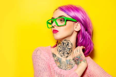 Attraktive junge Frau mit karminroten Haaren trägt eine leuchtend grüne Brille auf gelbem Hintergrund aufwirft. Helle Stil, Mode. Optik-Stil. Tätowierung. Haare färben.