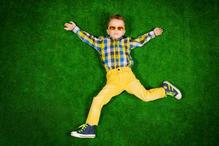 Smiling little boy in colorful clothes and sunglasses lying on a green lawn. Kid's fashion. Summer holidays.