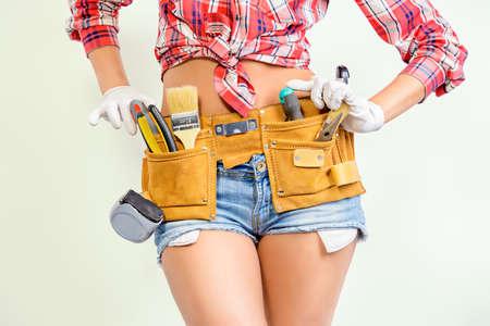Primer plano retrato de un trabajador de la construcción mujer que llevaba cinturón de herramientas. Edificio, el concepto de reparación. Foto de archivo