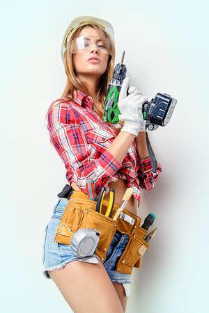 Aantrekkelijke jonge vrouw doet reparaties thuis. Portret van een vrouwelijke bouwvakker. De bouw, reparatie concept. Stockfoto - 63207749