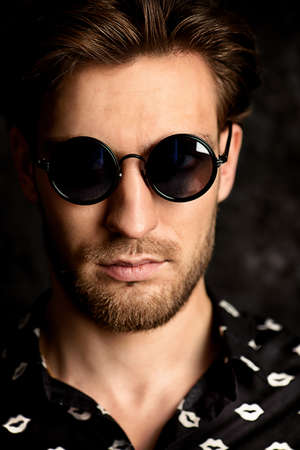 Portrait of a handsome young man in sunglasses. Men's beauty, fashion. Hairstyle.