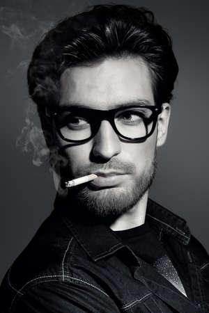 Ritratto in bianco e nero di un giovane di fumare. Bel giovane uomo pensieroso e con calma fumare una sigaretta. la bellezza maschile, moda.