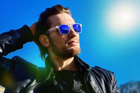 선글라스와 푸른 하늘 위로 가죽 자 켓에 자신감이 잘 생긴 남자가있다. 남자의 아름다움, 패션. 야외 초상화입니다. 스톡 콘텐츠