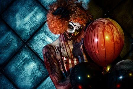 Evil roodharige clown bevlekt met bloed Holding ballonnen. Vrouwelijke zombie clown. Halloween. Verschrikking.