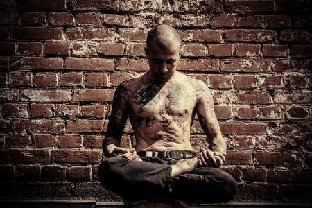 ヨガの概念。経験豊富なヨガのマスターは、レンガの壁で街の通りに座っている蓮華座で瞑想します。 写真素材
