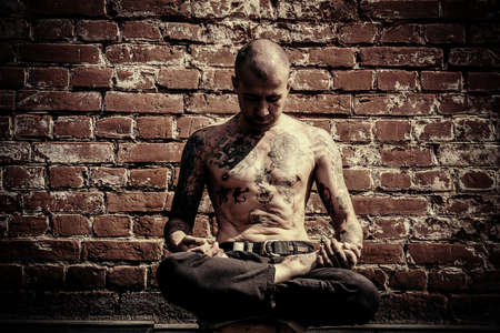 Yoga concept. Ervaren yogameester mediteert in de lotushouding zitten op een straat in de stad door de bakstenen muur.