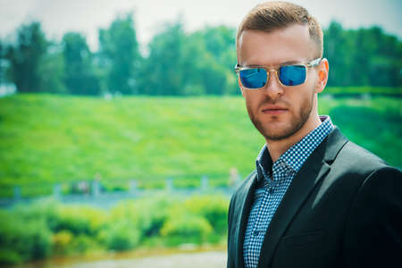 Close-up portrait of handsome man in a suit and sunglasses outdoor. Men's fashion.