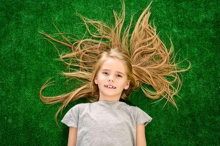 Lustige kleine Mädchen auf einem grünen Rasen liegen und Glück ausdrücken. Kindermode. Sommerferien.