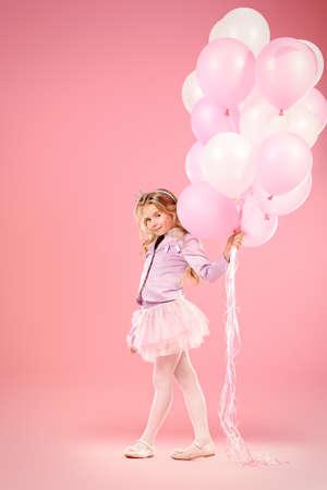 Niña bonita con hermosa atractiva pelo rubio con globos de color rosa sobre fondo de color rosa. Pequeña princesa con una corona en su cabeza. moda infantil.