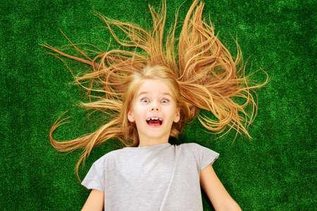 Lustige kleine Mädchen auf einem grünen Rasen liegen und zum Ausdruck bringen Überraschung und Glück. Kindermode. Sommerferien. Standard-Bild