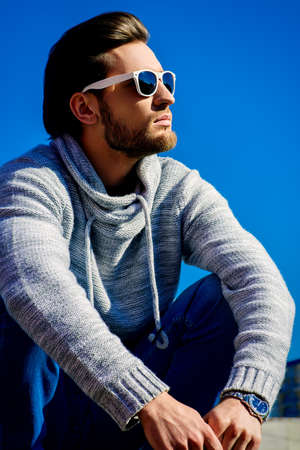Young handsome man in casual clothes and sunglasses over blue sky. Men's beauty, fashion. Outdoor portrait.