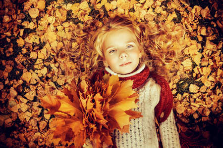 Pretty girl with a bunch of yellow leaves in the beautiful autumn park. Children's fashion.