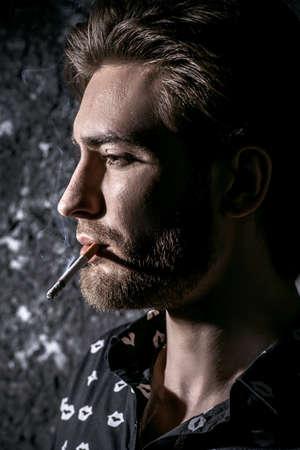 Fumo giovane. Bel giovane uomo pensieroso e con calma fumare una sigaretta. la bellezza maschile, moda.