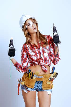 Attraente giovane donna che fa le riparazioni in casa. Ritratto di un operaio edile femminile. Costruzione, concetto di riparazione.