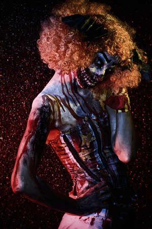 Evil clown murderer stained in blood. Female zombie clown. Halloween. Horror.