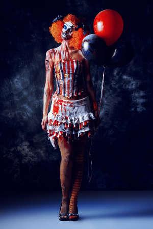 악마 빨간 머리 광대 풍선을 들고 혈액에 스테인드. 여성 좀비 광대입니다. 할로윈. 공포.