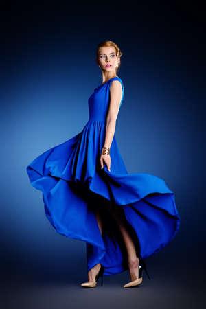 Retrato de una mujer joven y bella en elegante vestido de noche que presenta en movimiento en el estudio. Peinado.