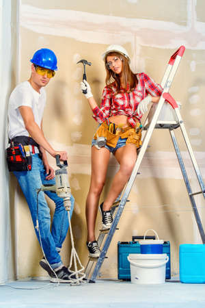 Male and female construction workers. Smiling young couple in love is going to renovate their new apartment. Stock Photo