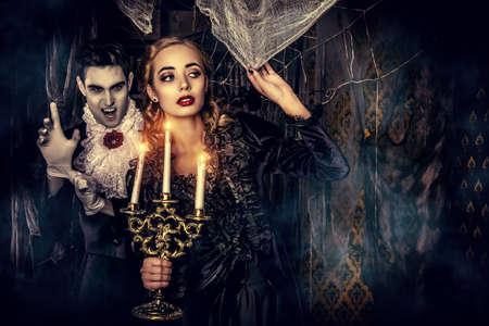 Krwiożerczy wampir mężczyzna w średniowiecznej sukni skrada się młodą piękną damę. Halloween.