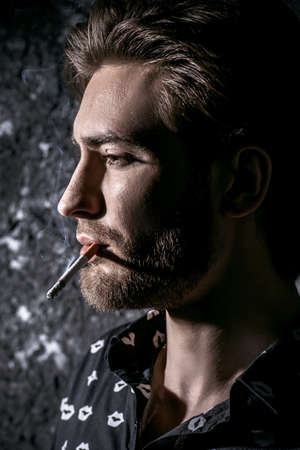 Smoking young man. Handsome young man thoughtfully and calmly smoking a cigarette. Men's beauty, fashion. Archivio Fotografico