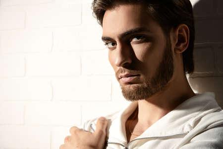 Ritratto di bellezza di un bel pensieroso giovane uomo in piedi da un muro di mattoni bianchi. la bellezza maschile, moda.