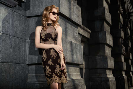 美しいファッション街に立っている女性。ヴォーグの撮影。