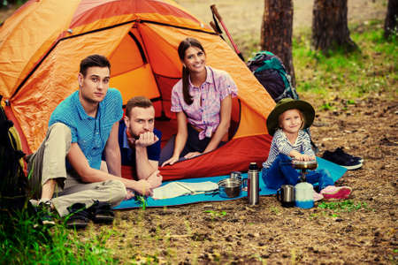 Friends resting in a camping tent in the forest. Active outdoor recreation.