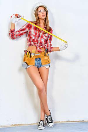 セクシーな若い女性のことを家で修復します。魅力的な女性建設労働者の肖像画。建物は、概念を修復します。