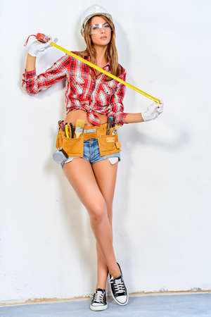 Mujer joven y atractiva que hace reparaciones en el hogar. Retrato del trabajador de la construcción mujer atractiva. Edificio, el concepto de reparación. Foto de archivo - 65036240