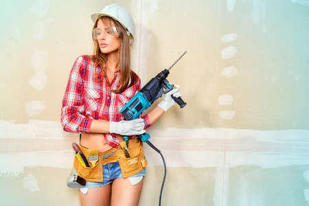 Aantrekkelijke jonge vrouw doet reparaties thuis. Portret van een vrouwelijke bouwvakker. De bouw, reparatie concept. Stockfoto - 65036242
