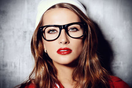 Attractive young woman in glasses and knitted cap. Red lipstick. Hipster style. Youth fashion. Фото со стока
