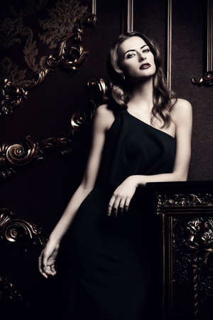Beautiful young woman wearing black evening dress standing by a fireplace in luxurious apartments. Glamorous woman. Vintage style.