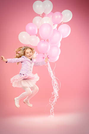 Pretty little girl with beautiful blonde hair jumping with pink balloons over pink background. Little princess with a crown on her head. Kids fashion.