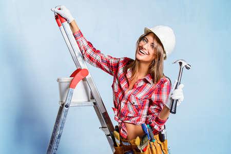 Abbastanza giovane donna che fa le riparazioni in casa. Ritratto di un operaio edile femminile. Costruzione, concetto di riparazione. Archivio Fotografico - 65645223
