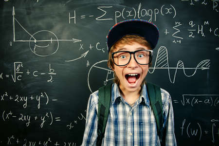 Education, high school, college. Portrait of a funny shouting student boy standing by a school blackboard. 스톡 콘텐츠