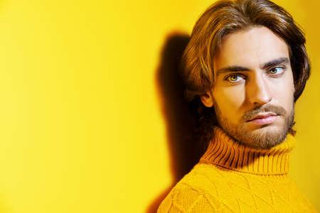 Gut aussehender Mann mit gelbem Pullover. Männer Schönheit, Mode. Frisur für Männer. Gelber Hintergrund.