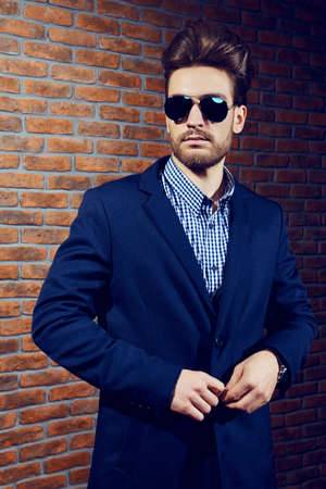 Portrait of a well-dressed imposing man in sunglasses. Fashion hair styling, barbershop. Brick wall background. Stock Photo